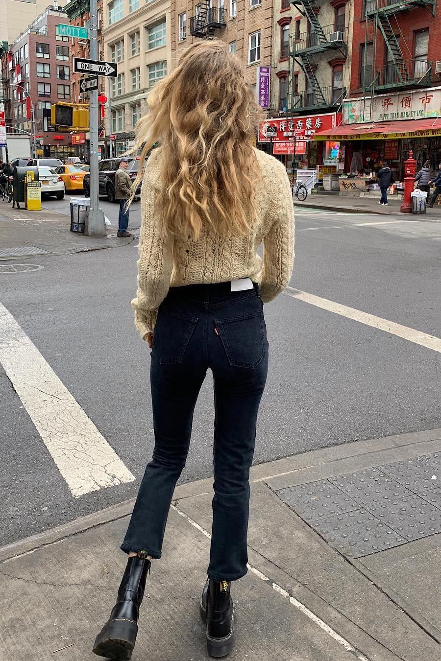 cable knit sweater with jeans and combat boots