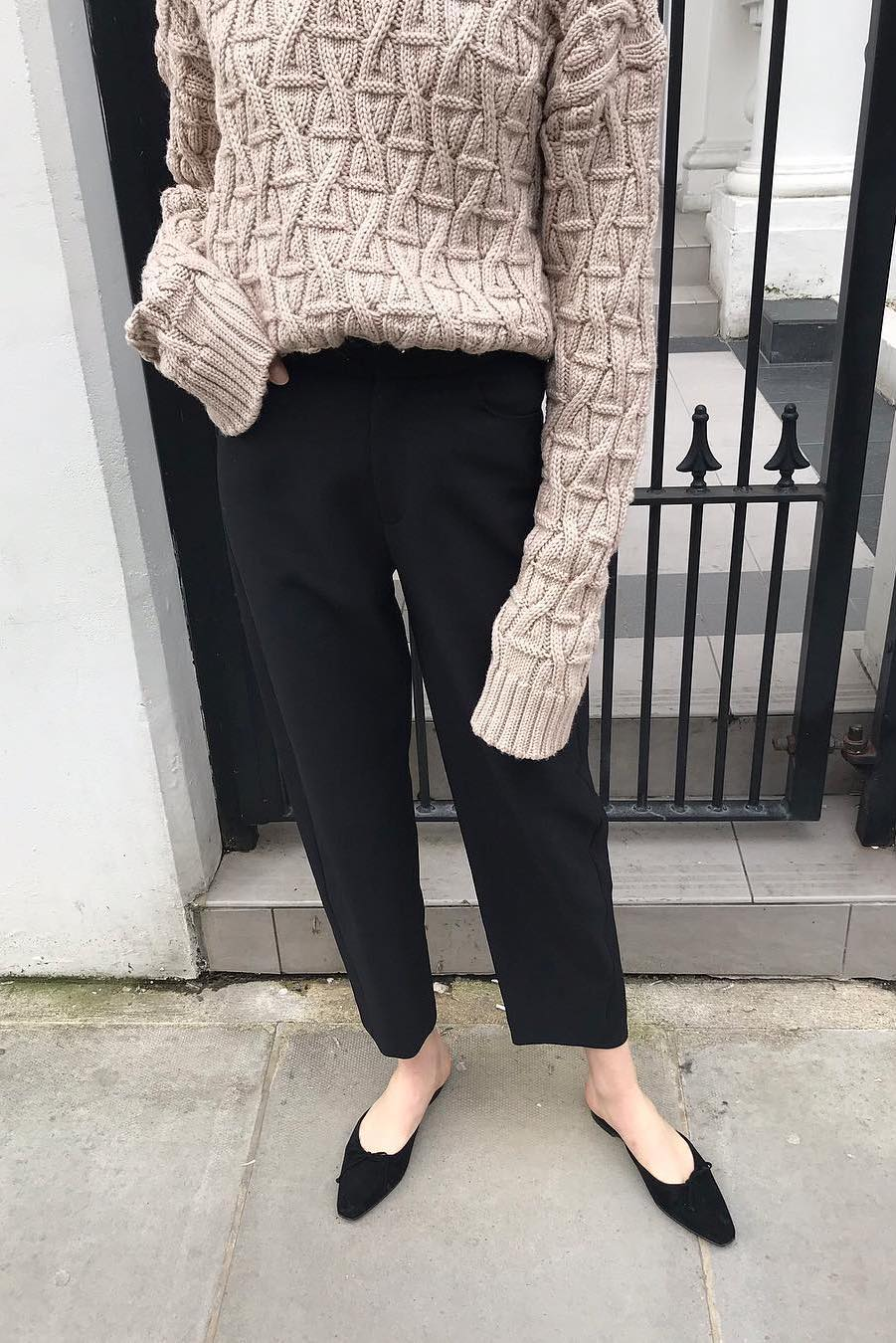 black trousers with beige cable knit sweater Toteme